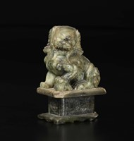 A green and russet jade figure of Pho dog, China,  ...