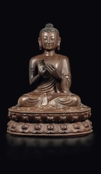 A wooden figure of Buddha seated on a double  ...